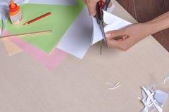La muchacha corta con las tijeras, papel coloreado, sentándose en la tabla imágenes de archivo libres de regalías