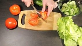 La muchacha corta los tomates almacen de metraje de vídeo