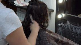 La muchacha corta su pelo en el peluquero Ella se sienta delante del espejo, y las tijeras del mujer-peluquero cortan los extremo almacen de video