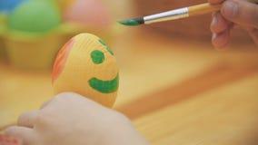 La muchacha creativa eligió verde pintar La muchacha preciosa está dibujando una sonrisa verde en el huevo de Pascua Concepto de
