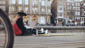 la muchacha creativa joven 4K se sienta con el ordenador portátil afuera El blogger del arte de la moda trabaja al aire libre Lib almacen de video