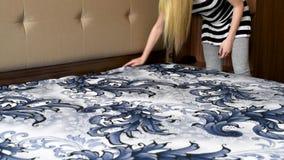 La muchacha cubre la cama con nuevo lino, contra la perspectiva de otros muebles metrajes