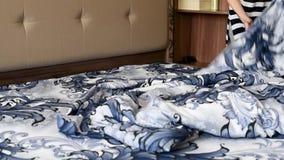 La muchacha cubre la cama con nuevo lino, contra la perspectiva de otros muebles almacen de metraje de vídeo