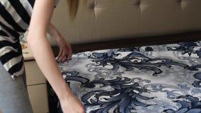 La muchacha cubre la cama con nuevo lino, contra la perspectiva de otros muebles almacen de video