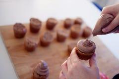 La muchacha cubre la torta con crema Proceso de cocinar las magdalenas, los molletes y los ingredientes para la decoración en la  foto de archivo libre de regalías