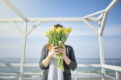 La muchacha cubre su cara con los tulipanes amarillos imágenes de archivo libres de regalías