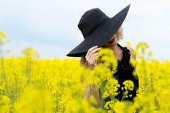 La muchacha cubrió su cara con un sombrero en el campo con las flores Fotos de archivo