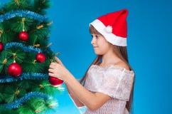 La muchacha cuelga para arriba un juguete en un abeto Fotografía de archivo