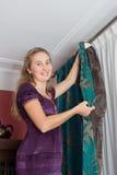 La muchacha cuelga para arriba una cortina fotografía de archivo libre de regalías