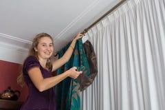 La muchacha cuelga para arriba una cortina fotos de archivo libres de regalías