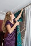 La muchacha cuelga para arriba una cortina imágenes de archivo libres de regalías