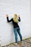 La muchacha cuesta cerca de una pared blanca Foto de archivo libre de regalías