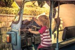 La muchacha curiosa del mecánico del niño que conduce la moto del tuk del tuk durante niños del concepto de Asia Tailandia del vi foto de archivo libre de regalías