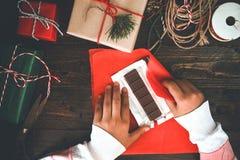 La muchacha da el embalaje del regalo por regalos de Navidad y Año Nuevo Imagen de archivo