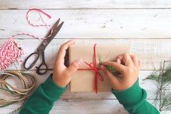 La muchacha da el embalaje del regalo por regalos de Navidad y Año Nuevo Imágenes de archivo libres de regalías