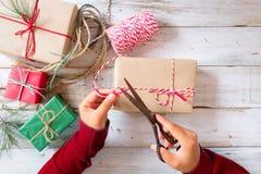 La muchacha da el embalaje del regalo por regalos de Navidad y Año Nuevo Fotos de archivo
