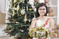 La muchacha da el regalo de la Navidad Imagen de archivo libre de regalías