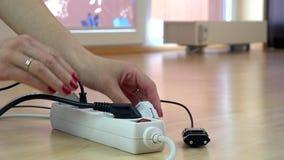 La muchacha da los alambres de los enchufes del interruptor de la electricidad almacen de video