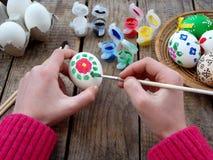 La muchacha da los huevos de la pintura con aguazo de los estampados de flores Adornamiento del huevo Preparación para Pascua Foto de archivo