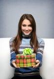 La muchacha da un regalo foto de archivo