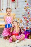 La muchacha da un regalo a su hermana que se sienta en la manta delante del árbol de navidad Imagenes de archivo