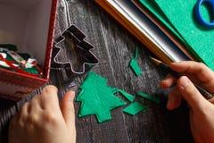 La muchacha da vuelta al árbol de navidad verde hecho de tela Imagen de archivo