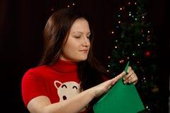 La muchacha da vuelta al árbol de navidad verde hecho de tela Foto de archivo libre de regalías