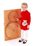 La muchacha da vuelta al engranaje rueda a mano adentro a Montessori fotografía de archivo