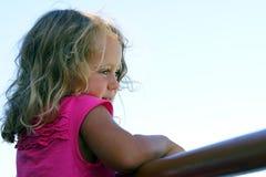 La muchacha de 3-4 años considera con interés algo imagenes de archivo