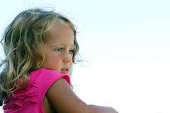 La muchacha de 3-4 años considera con interés algo imágenes de archivo libres de regalías