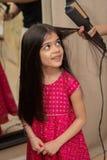 La muchacha de 6 años hace que su pelo sea enderezado por su madre en casa imágenes de archivo libres de regalías