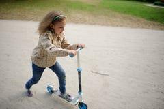 La muchacha de 7-8 años monta una vespa Imagen de archivo