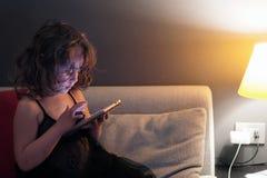 La muchacha de 3-4 años utiliza el teléfono celular en la noche fotografía de archivo libre de regalías