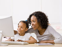 La muchacha de ayuda de la madre hace la preparación en el ordenador Foto de archivo libre de regalías