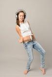 La muchacha de baile con los auriculares que canta disfruta de música Imagen de archivo libre de regalías