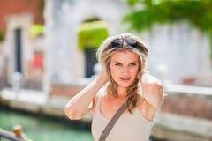 La muchacha de Beautful está presentando por el río en Venecia, Italia Foto de archivo