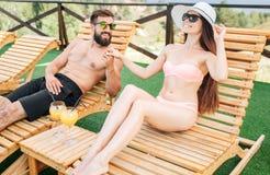 La muchacha de Beautiflu se está sentando en sunbed Ella lleva el sombrero y las gafas de sol La muchacha señala adelante El indi imagenes de archivo