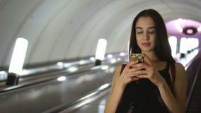 La muchacha de la belleza abajo de la escalera móvil en subterráneo, leyó el mensaje en sonrisa del teléfono móvil almacen de video