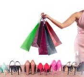 La muchacha de bolsos hace por completo compras en una tienda Imágenes de archivo libres de regalías