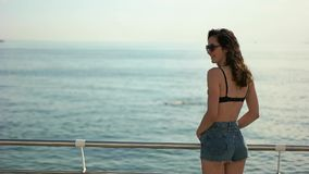 La muchacha de Brunete en pantalones cortos mira el mar almacen de metraje de vídeo