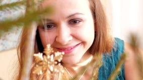 La muchacha de la cámara lenta admira el copo de nieve del oro en el árbol de navidad metrajes