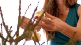 La muchacha de la cámara lenta adorna el árbol de navidad con las bolas del oro almacen de metraje de vídeo