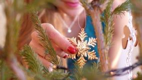 La muchacha de la cámara lenta adorna el árbol de navidad con los copos de nieve almacen de video