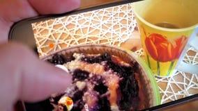 La muchacha de la cámara lenta toma la foto de la torta y de la taza de té deliciosas almacen de video