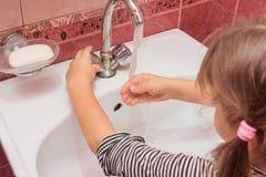 La muchacha de cinco años ajusta flujo y la temperatura deseados del agua que fluye del grifo en el fregadero Imagen de archivo