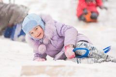 La muchacha de cinco años cayó en la nieve rodó abajo una colina y rodeada por otros niños Fotos de archivo libres de regalías