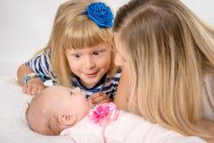 La muchacha de cinco años con el asombro mira a su hermana recién nacida Imagenes de archivo