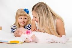 La muchacha de cinco años está mirando a su madre que esté mirando a la hija recién nacida Imagenes de archivo