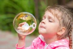 La muchacha de cinco años infla la burbuja circular grande Foto de archivo libre de regalías