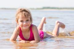 La muchacha de cinco años miente en agua en los bajos del río y de mirar el marco Foto de archivo